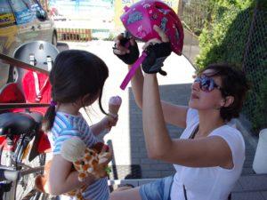 zdjęcie mamy zakładającej kask rowerowy dziecku