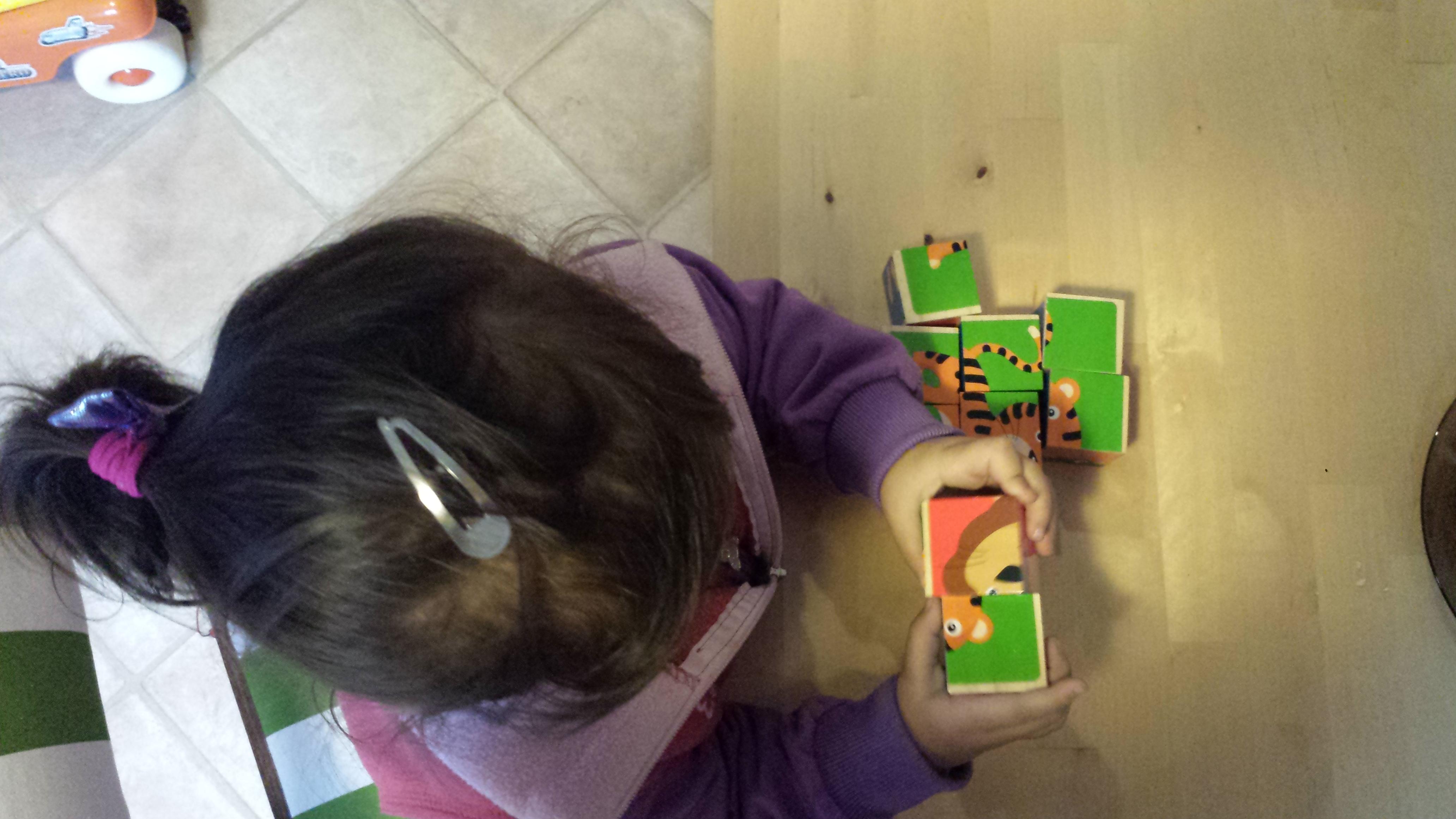 zdjęcie dziecka układającego puzzle sześcienne