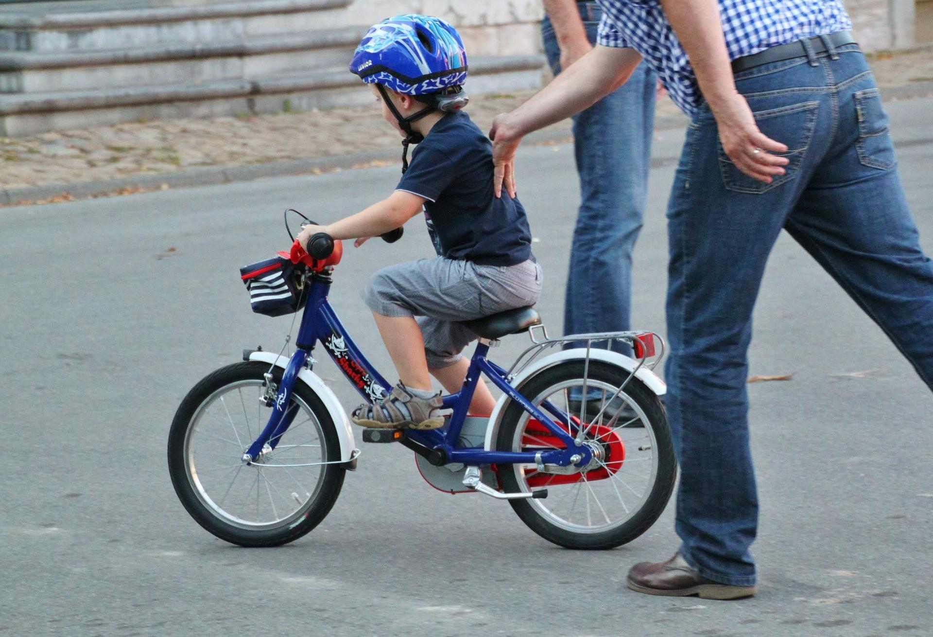 zdjęcie dziecka uczącego się jazdy rowerem