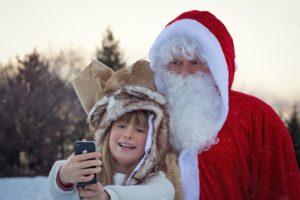 Zdjęcie dziewczynki robiącej zdjęcie z Mikołajem