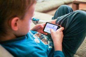 zdjęcie dziecka grającego na telefonie